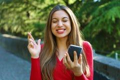 Fingeres que cruzan de la muchacha esperanzada que llevan a cabo noticias que esperan del smartphone para al aire libre Mujer jov foto de archivo libre de regalías