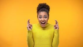 Fingeres que cruzan del suéter amarillo emocionado del estudiante, haciendo deseo, expectativa fotos de archivo