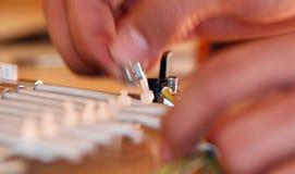 Fingeres que fijan los tornillos Imágenes de archivo libres de regalías