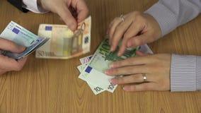 Fingeres que golpean en los billetes de banco euro de la tabla y del gancho agarrador para la mano del hombre metrajes