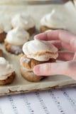 Fingeres que sostienen la galleta de torta dulce con el merengue Fotografía de archivo