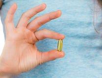 Fingeres que sostienen una cápsula del aceite de pescado Imágenes de archivo libres de regalías