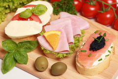 Fingerfood. Topped with ham, smoked salmon and caviar, tomatos and mozzarella cheese royalty free stock photo