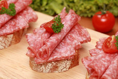Fingerfood with salami. Fingerfood topped with salami and tomatoes stock photo