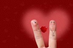 Fingerkunst eines glücklichen Paars Mann gibt Herz Auf lagerbild Lizenzfreie Stockfotos