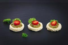 Fingermat för för Canapepesto för parti hemlagad tomat för sås överst och persilja spricker ut Arkivbild
