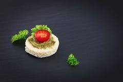 Fingermat för för Canapepesto för parti hemlagad tomat för sås överst och persilja spricker ut Arkivbilder