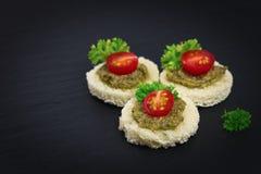 Fingermat för för Canapepesto för parti hemlagad tomat för sås överst och persilja spricker ut Fotografering för Bildbyråer