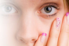 Fingernails. Coloured pink female fingernails in the face with eye Royalty Free Stock Photography