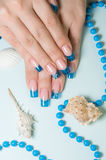 Fingernails with blue french manicure. On decorated background stock photography