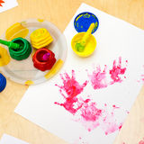 Fingerpaint. White paper with child handprints on on a table stock image
