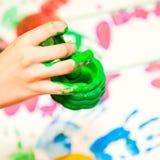 Fingerpaint. Child holding finger paint brush close-up stock photos