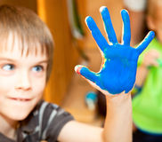 Fingerpaint. Happy boy ready to do a hand print royalty free stock image