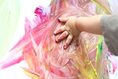 Fingerpainting. Child hand fingerpainting on a canvas, bright colors, art, sensory experience Stock Photography