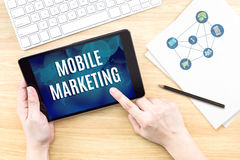 Fingerpekskärm med mobilt marknadsföringsord med tangentbordet och arkivfoton