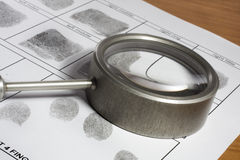 Fingerprint card. Magifying glass inspecting a fingerprint royalty free stock images