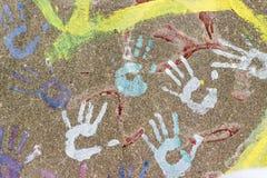 Fingerprints of children`s hands. Colored fingerprints of children`s hands on asphalt Royalty Free Stock Photography