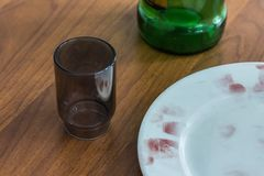 Close-up of a plate, a glass, a bottle on a wooden table at the crime scene. Fingerprints on the edge of the dish are covered with stock images