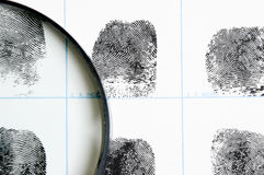 Fingerprints and magnifying glass Stock Images