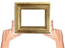 Fingerrahmen und hölzerner goldener Rahmen lokalisiert auf Weiß Stockfotografie