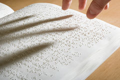 Fingers above a braille book Royalty Free Stock Images