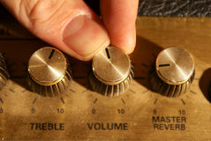 Fingers adjusting a volume knob Royalty Free Stock Photos