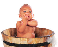 Fingers, Arms, Nose. An adorable biracial baby bathing in a wooden tub with his arms twisted, his fingers curled into his mouth and under his nose.  Isolated on Stock Photo