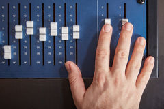 Fingers of audio engineer pushing the faders of an auio mixer Royalty Free Stock Photos