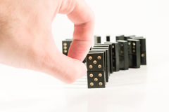 Fingers and black dominoes. Human fingers ready to push a row of black dominoes (on white Stock Images
