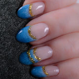 Fingers with blue french manicure and gold glitter Royalty Free Stock Images