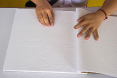 Fingers and braille. blind people read a book in braille. Royalty Free Stock Photo