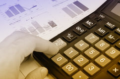 Fingers on calculator Stock Images