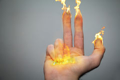 Fingers of candles. A right hand and fingers are on fire like candles or torches. Being an inspiration of the Hanukiah (menorah). 8 fingers symbolizing the Royalty Free Stock Image