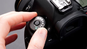 Fingers changing shooting mode on a camera royalty free stock photos