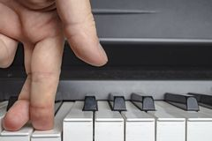 Fingers click on the piano keys as if the legs. Close-up stock photo