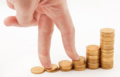 Fingers climbing at the coins Royalty Free Stock Photos