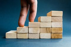Fingers climbing the stairs made with wooden blocks. Concept of the success, career, goal achievement, hardworking. Fingers climbing the stairs made with wooden Stock Image
