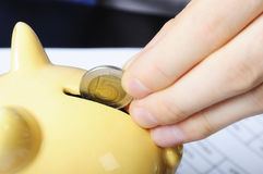 Fingers, coin and piggybank Stock Images