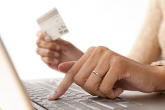 Fingers on Computer with Credit Card. Close up of woman's fingers on computer keyboard while holding credit card Stock Image