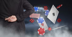 Fingers crossed behind back with poker chips and playing cards Royalty Free Stock Photos
