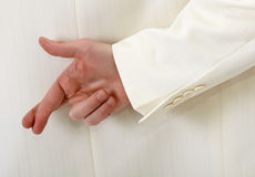 Fingers crossed behind back - white suit Royalty Free Stock Photos