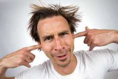 Fingers In Ears. Scruffy unpleasant looking man with a silly facial expression and unruly hair puts his fingers in his ears so that he can not hear Royalty Free Stock Images