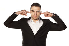 Fingers in ears. Young and attractive serious businessman in black suit, clog his ears with fingers royalty free stock photo
