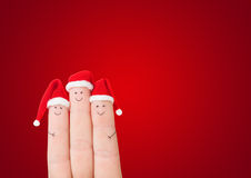 Fingers faces in Santa hats against red background Royalty Free Stock Photography