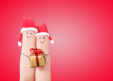 Fingers faces in Santa hats with gift box. Happy couple celebrating concept Stock Photos