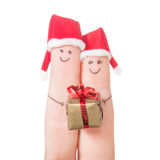Fingers faces in Santa hats with gift box. Stock Images