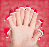 Fingers faces in Santa hats. Happy family celebrating concept Royalty Free Stock Photo