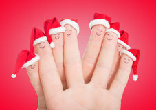 Fingers faces in Santa hats. Happy family celebrating Stock Image