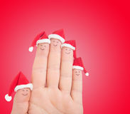 Fingers faces in Santa hats. Happy family celebrating Stock Photos