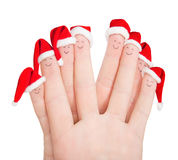 Fingers faces in Santa hats isolated against white. Happy friend Royalty Free Stock Photo